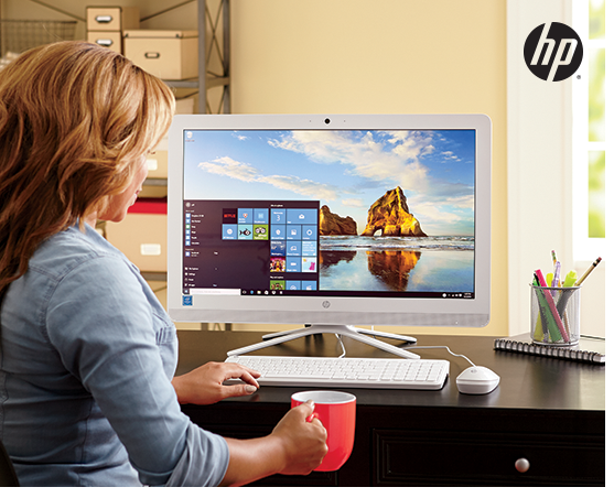 """Woman relaxing at desk in home office, looking at a 23.8"""" all-in-one Windows PC by HP"""