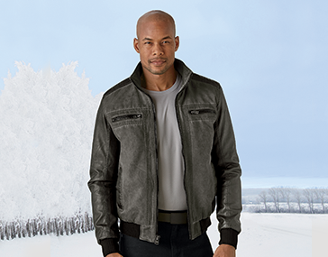 Man standing outside in snow-covered countryside, wearing our gray Dark Rider Jacket