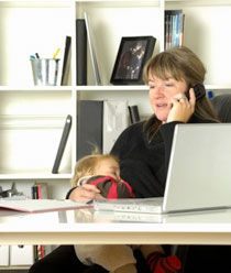 Mother breastfeeding a young child while working
